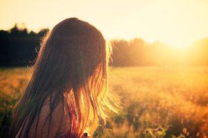 Kvinna i solnedgång blickar framåt mot miljömål